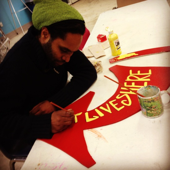 Artist Nehemiah Dixon III working on the Art Lives Here arrow