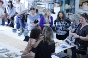 A crowd gathers around Red Dirt Studios founder Margaret Boozer during Gateway CDC's 10th Annual Open Studios Tour